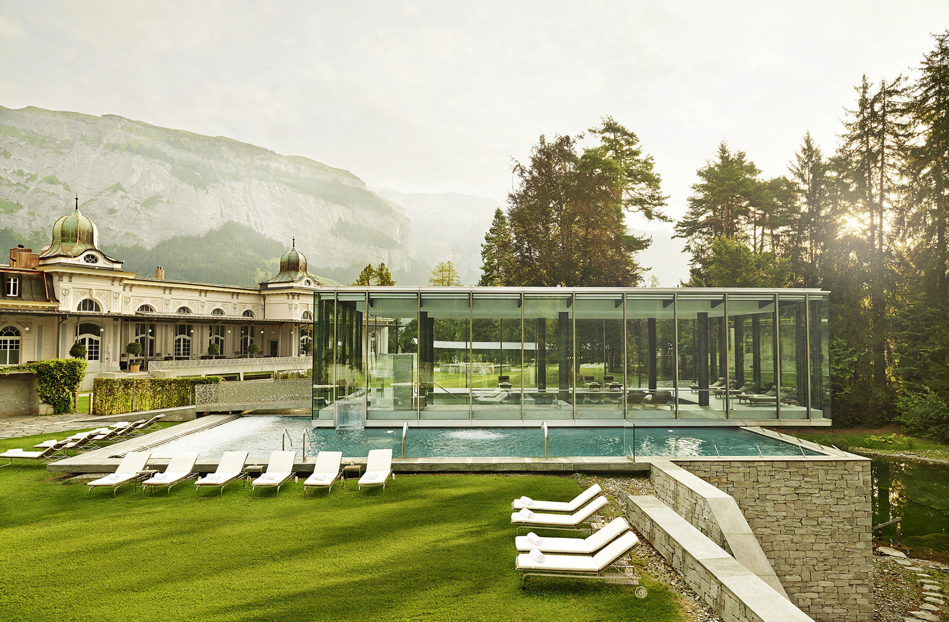 exterior shot of the waldhaus flims spa building and pool. The building is white with decorative fixtures at the top. The pool is indoor and outdoor. The indoor portion of the pool is encased in a glass fixture. The outside portion of the pool is lined with white lounge chairs. In the distance are evergreen trees and the swiss alps.