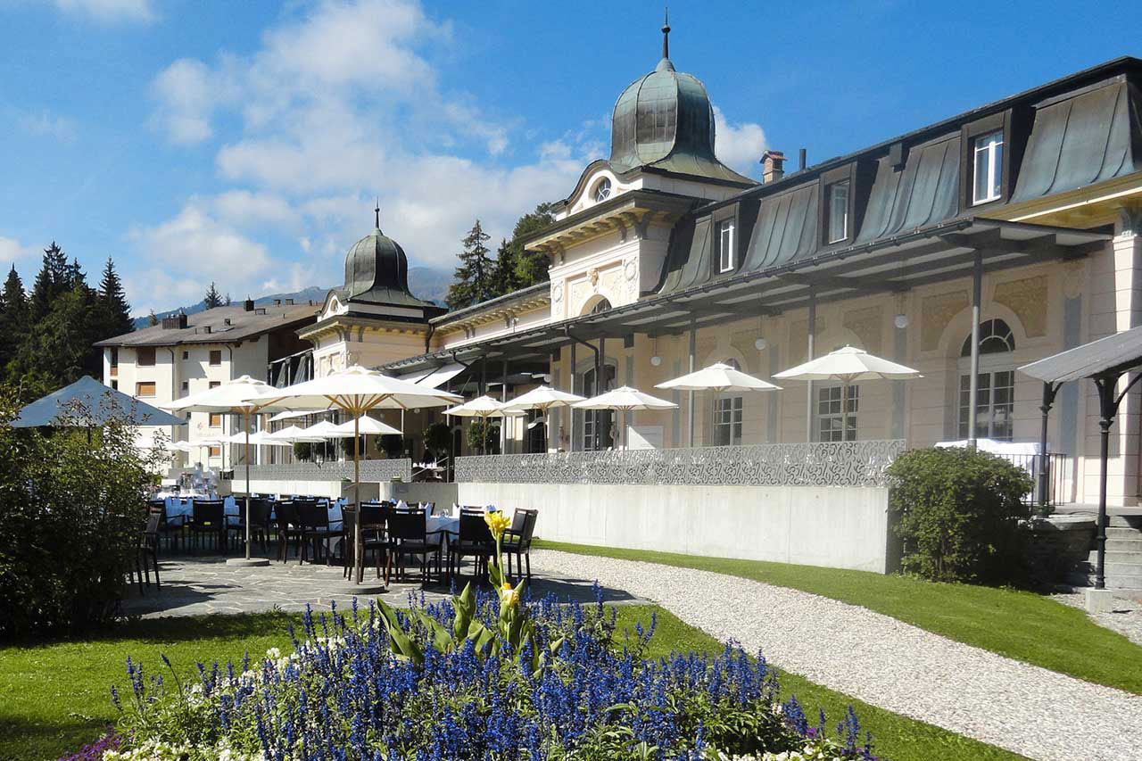 exterior shot of the waldhaus flims resort spa building and a garden seating patio. The building is white and gray with decorative fixtures. White umbrellas line the walkway outside the building and black dining chairs circle tables donned in white cloth. Surrounding the dining area are flower beds with blue, white and yellow flowers. In the distance are evergreen trees and the tops of the swiss alps.