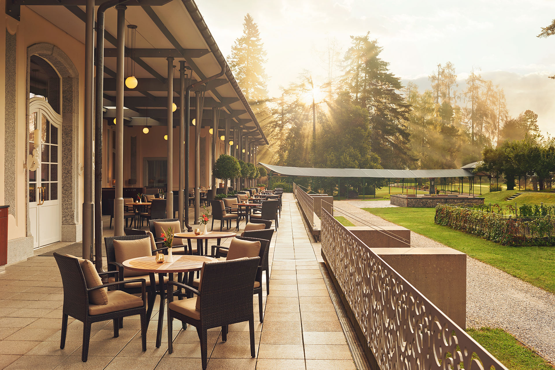 exterior shot of an outdoor dining patio. the patio is lined with black woven chairs with tan cushions surrounding light brown round table tops. There is a candle and a floral arrangement at each table. The patio overlooks the lush green grounds. In the background there are large evergreen trees with the sun shining through.