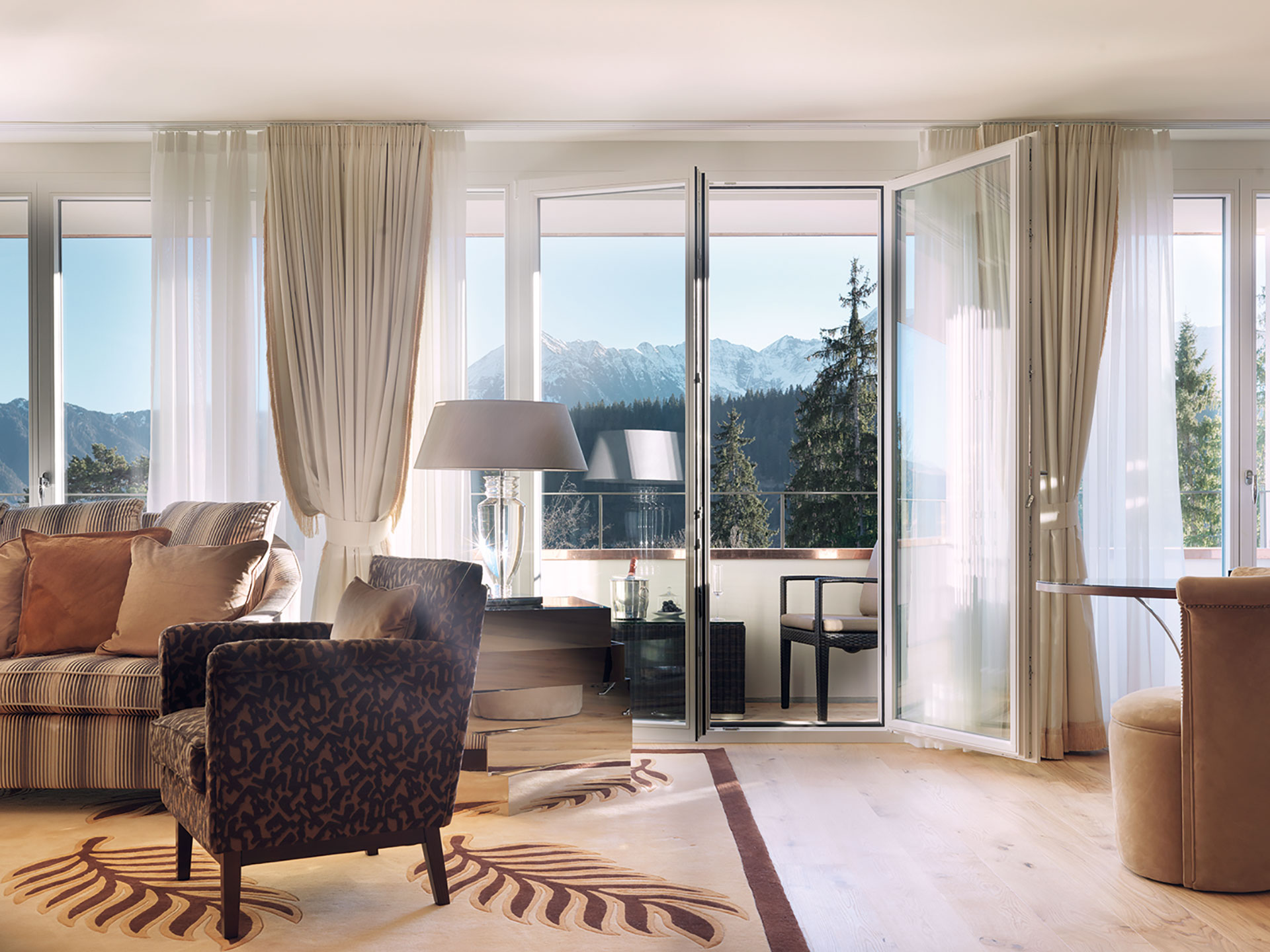 an interior shot of a sitting room in a suite. There is a striped couch and black and brown patterned chair in the corner of the room. The are glass doors leading out onto a balcony overlooking the evergreen trees and the tops of the swiss alps.