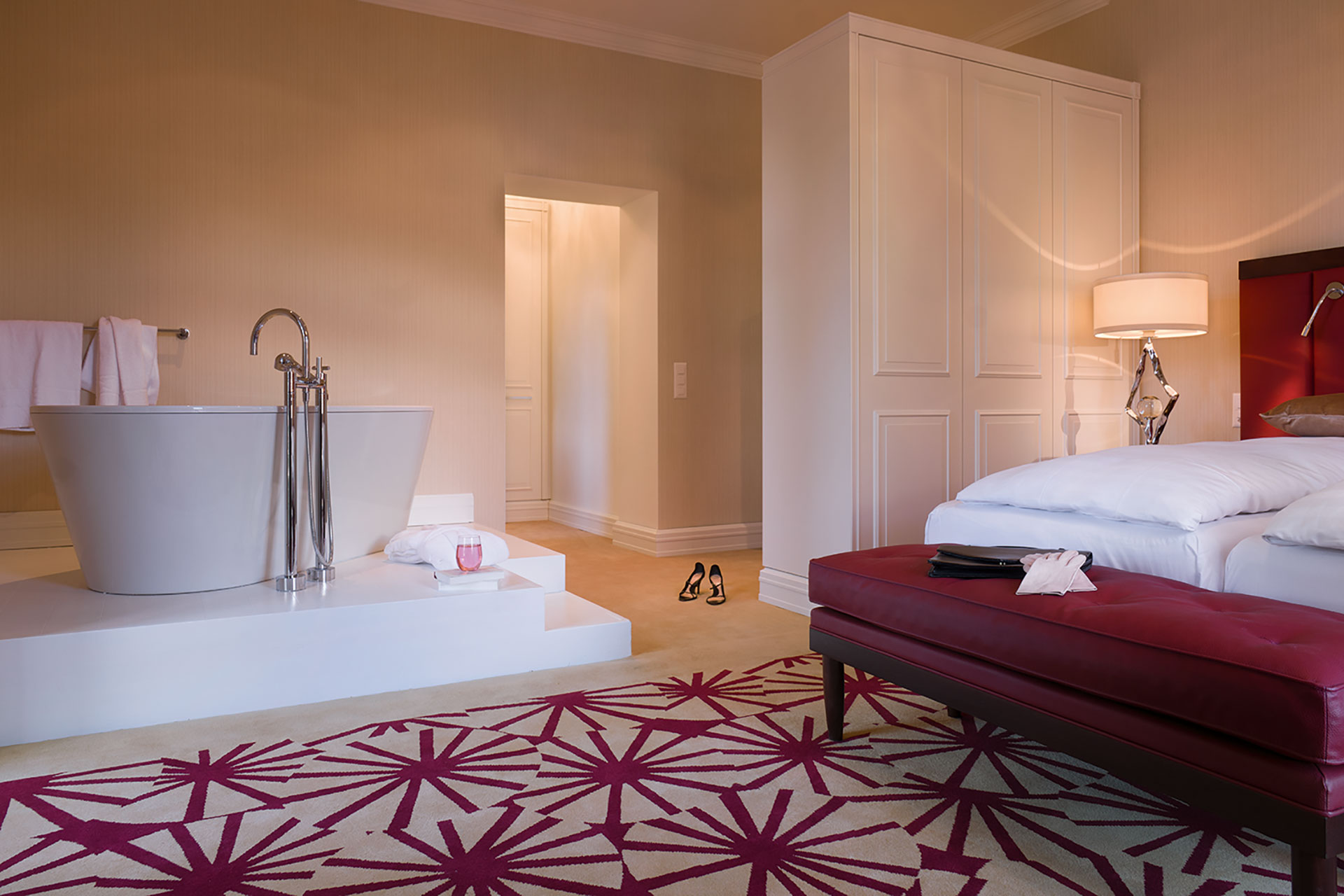 an interior shot of a two bed suite. The two beds are donned in white linens and there are accents of red around the room in the headboards, bench, and carpet. There is a white stand alone tub in the corner of the room.