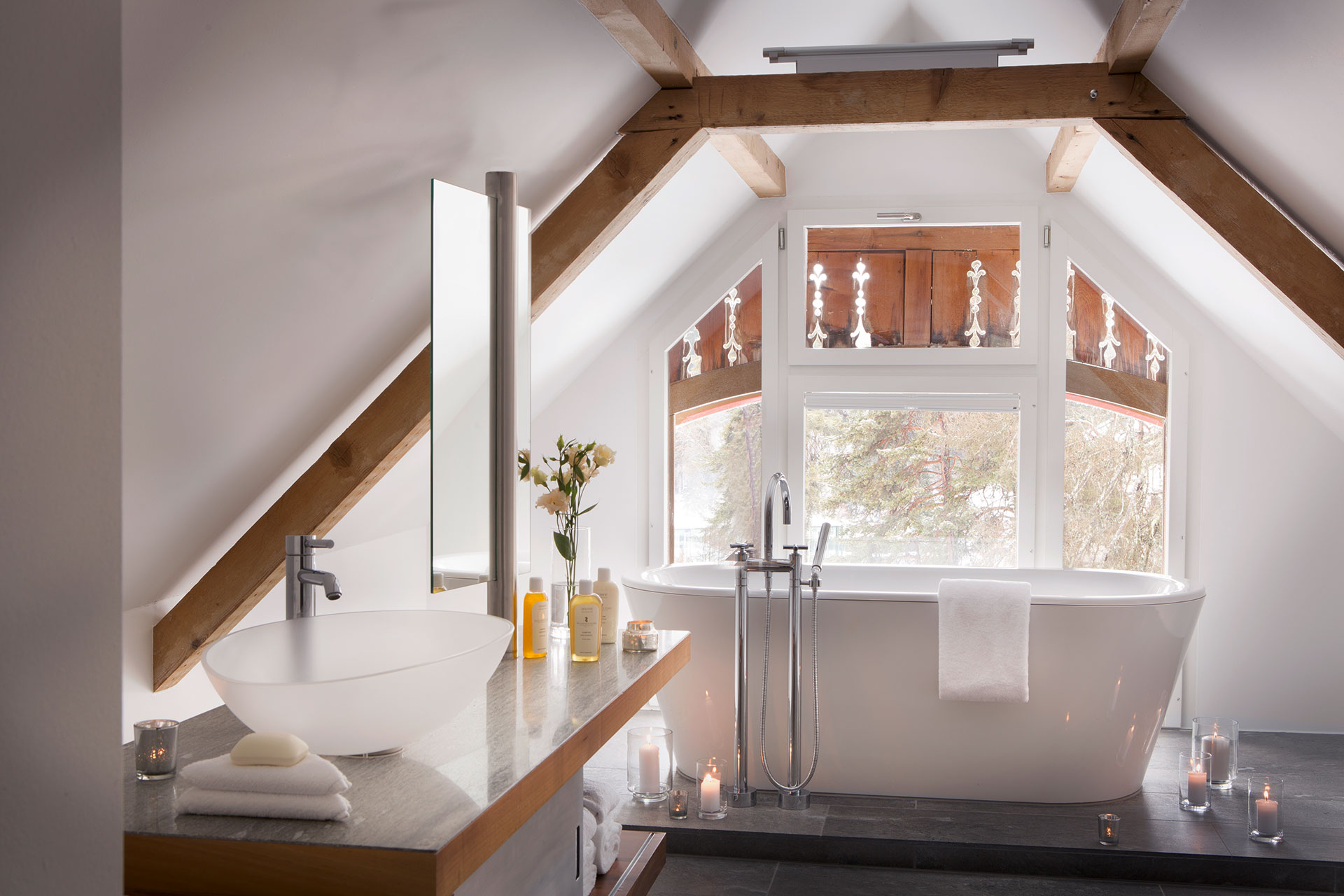 interior shot of a bathroom in a suite. The walls are slanted giving the room a cozy feel. The walls are white and the exposed beams are a light wood. There is a stand alone bathtub overlooking the view of the forest surrounding the property. The sink and mirror rests on a light wood countertop. There are candles and toiletries placed around the room