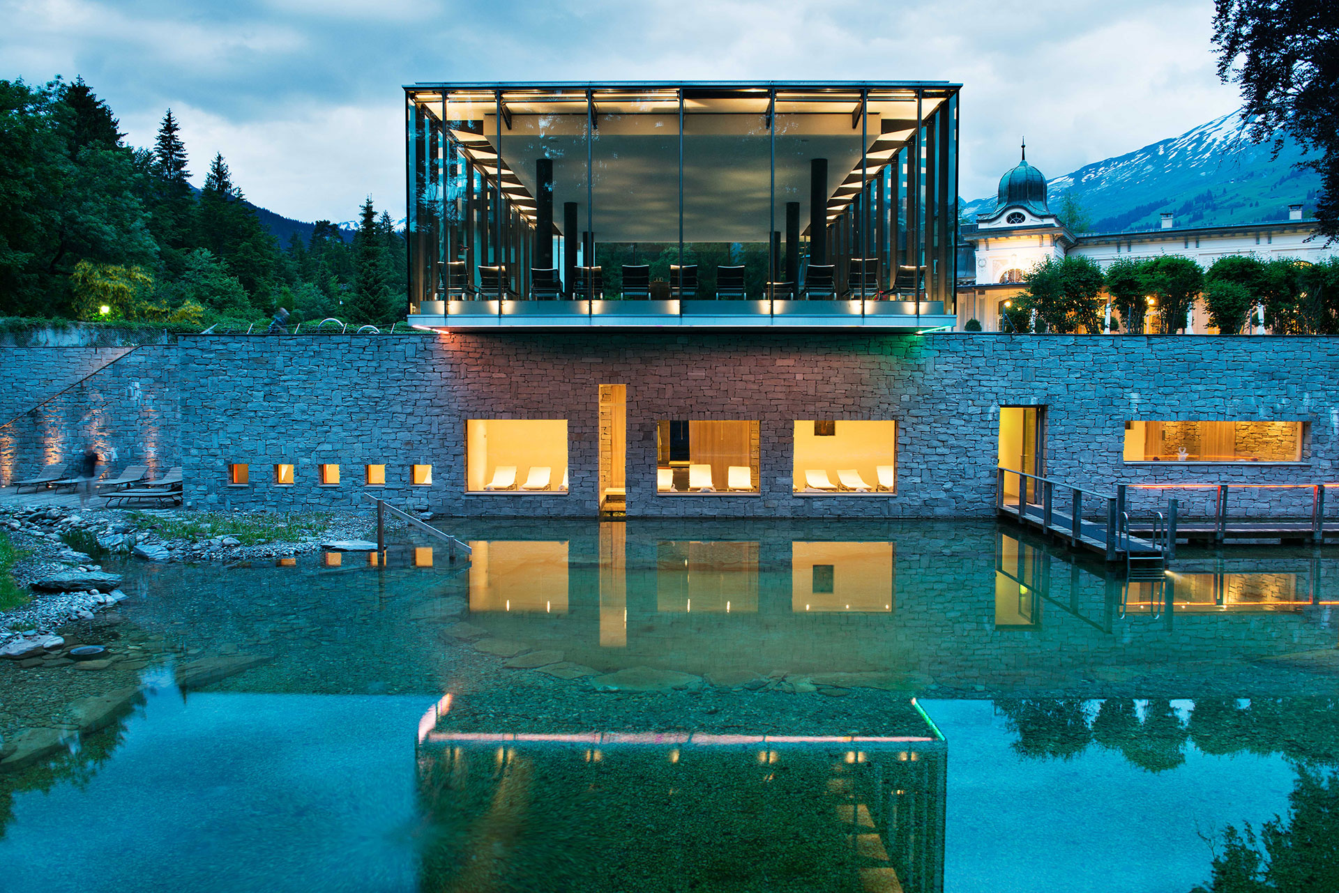 an exterior shot of the resort's spa and outdoor pool. The building is modern and layered. The pool is natural, blending seamlessly into the surrounding nature. There are golden lights coming from the windows of the spa and it is reflecting off of the pool. In the distance are the evergreen trees and tops of the swiss alps.