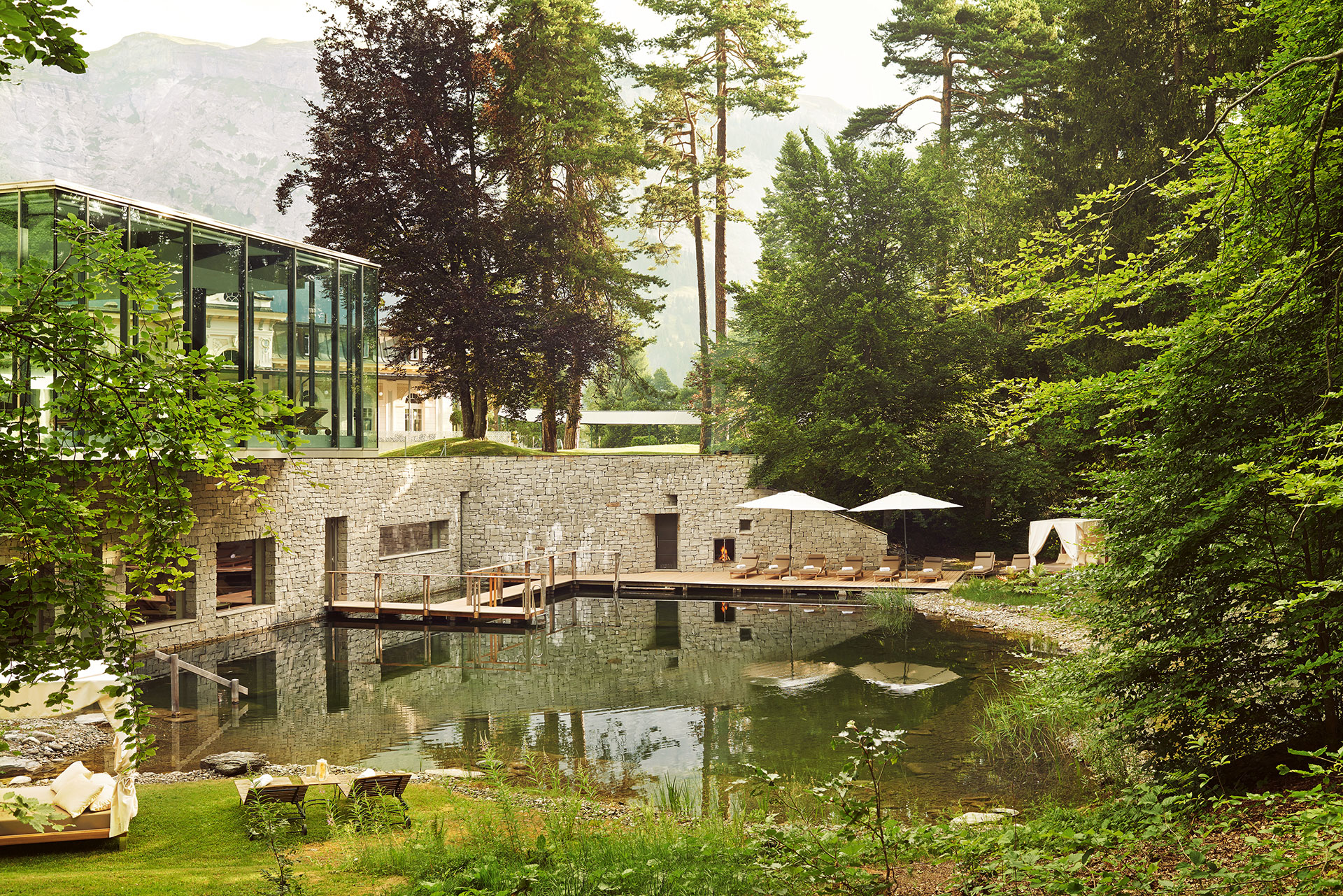 Landscape shot of the resort's pool. The pool is surrounded by lush greenery. The pool leads into the spa and there is a wooden bridge that leads guests inside to the outside and vice versa. Lining the pool are brown lounge chairs and white umbrellas. In the background there is a view of the swiss alps